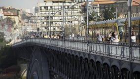 Folk som går på bron nära spårvagnen lager videofilmer
