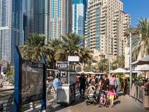 Folk som går på Dubaien Marine Walk i marina  Arkivfoton