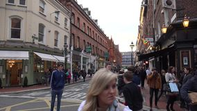 Folk som går på en upptagen gata i Dublin lager videofilmer