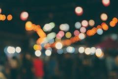 Folk som går på gatan och ljuset som gör suddig bakgrunden och bokehen fotografering för bildbyråer