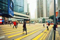 Folk som går på gator med högväxt exponeringsglas, och konkreta byggnader i upptaget område Arkivbild