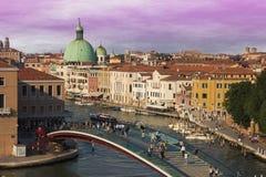 Folk som går på konstitutionbron över kanalen som är stor av Venedig Arkivfoton