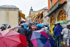 Folk som går på regnig dag med paraplyer på trappuppgång av den Rialto bron Ponte de Rialto i Venedig, Italien arkivfoto
