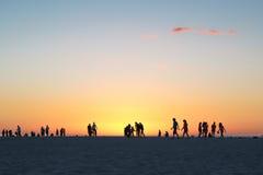 Folk som går på solnedgången Arkivbild