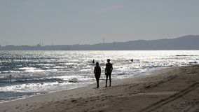 Folk som går på stranden med Piombino i bakgrunden lager videofilmer