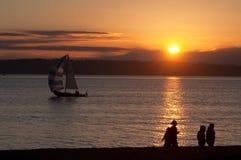 Folk som går på stranden med segelbåten Arkivbild