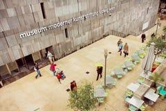 Folk som går runt om museum av modern konst med det utomhus- kafét i Museumsquartieren Arkivbild