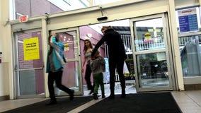 Folk som går till och med dörrarna på stormarknaden arkivfilmer