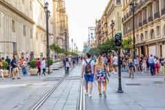 Folk som går under dagen i en fot- gata nära domkyrka i Seville, Spanien berömd landmark royaltyfria foton