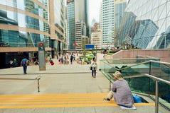 Folk som gör bilder och går runt om centrum med skyskrapor och moderna arkitekturstrukturer Arkivbild