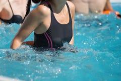 Folk som gör vattenaerobics i en utomhus- simbassäng Arkivfoton