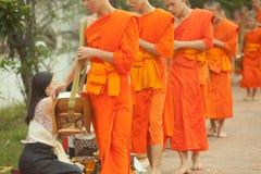 Folk som ger allmosa till buddistiska munkar på gatan, Luang Prabang, 20 JUNI 2014 Arkivbilder