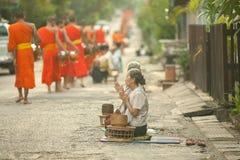 Folk som ger allmosa till buddistiska munkar på gatan, Luang Prabang, 20 JUNI 2014 Arkivbild