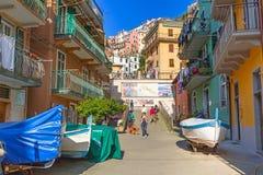 Folk som går på gatan av den Manarola byn i Italien Fotografering för Bildbyråer