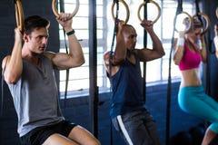 Folk som hänger från gymnastiska cirklar i idrottshall Royaltyfri Bild