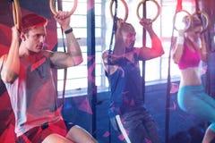 Folk som hänger från gymnastiska cirklar i idrottshall Arkivfoto