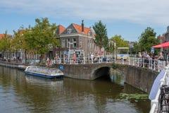 Folk som håller ögonen på den härliga historiska gamla kanalen i mitten av delftfajans, Nederländerna arkivfoto