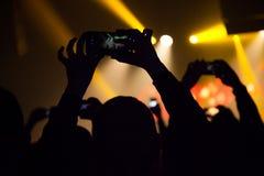 Folk som håller ögonen på en konsert och någon skyttefoto och video med en mobiltelefon royaltyfria bilder