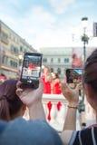 Folk som håller ögonen på en levande show ta foto och video Royaltyfria Bilder