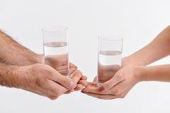 Folk som håller exponeringsglas med vatten royaltyfria foton