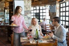 Folk som har den lantliga restaurangen för matställe royaltyfria bilder