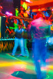 Folk som har gyckel i ett disko suddighetseffekt för ett konstnärligt handlag Arkivfoton