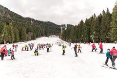 Folk som har gyckel på snöig berghimmelsemesterort Royaltyfri Bild