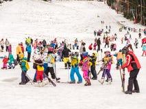 Folk som har gyckel på snöig berghimmelsemesterort Arkivfoto