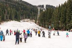 Folk som har gyckel på snöig berghimmelsemesterort Arkivbilder