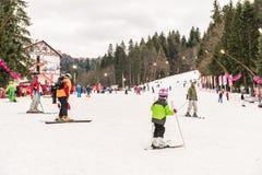 Folk som har gyckel på snöig berghimmelsemesterort Fotografering för Bildbyråer