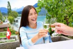 Folk som har gyckel som dricker vitt vin på matställen royaltyfria bilder