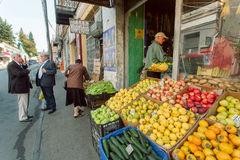 Folk som köper nya frukter och grönsaker i detaljist av den gamla staden Arkivbild