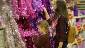 Folk som köper Xmas-leksaker och glitter på julmarknaden, moder och barn som väljer festlig garnering i shoppagallerian arkivfilmer
