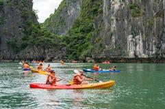 Folk som Kayaking i den Halong fjärden Arkivfoton
