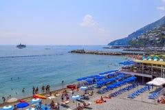 Folk som kopplar av, färgrikt paraply på stranden på en solig dag, på kusten av Amalfi, Italien Ett skepp, en eyeliner i det blåa Royaltyfri Fotografi