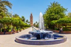 Folk som kopplar av i Koutoubia trädgårdar Marrakech Royaltyfria Foton