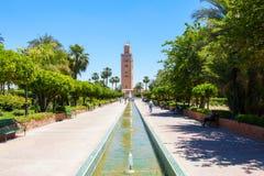 Folk som kopplar av i Koutoubia trädgårdar Marrakech Arkivfoto