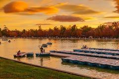 Folk som kopplar av i roddbåtar i det sceniska dammet av Buen Retiro PA Arkivfoto
