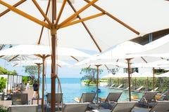 Folk som kopplar av och att tycka om en lyxig oändlighetssimbassäng i strandhotellet royaltyfria bilder