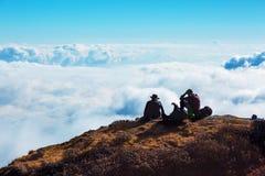 Folk som kopplar av på bergklippan som tycker om molnhimmelhorisonten royaltyfri foto