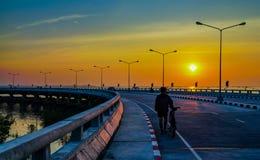Folk som kopplar av på den krökta kust- vägen med gatalampan och oran Royaltyfria Bilder
