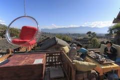 Folk som kopplar av på en soffa och tycker om sikten av Lijiang den gamla staden på en solig dag Royaltyfria Foton