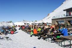 Folk som kopplar av på restaurangen på de schweiziska fjällängarna Royaltyfri Bild