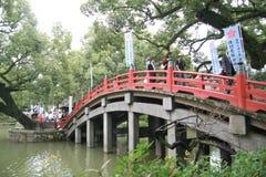 Folk som korsar den röda bron i den Dazaifu tenmanguen Arkivbild