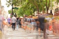 Folk som korsar den upptagna gatan Arkivfoton