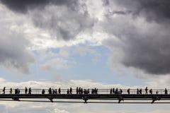 Folk som korsar en bro, över Thameset River Fotografering för Bildbyråer