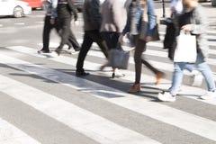 Folk som korsar en gata royaltyfri foto