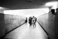 Folk som korsar en tunnel på den Paris tunnelbanan royaltyfri fotografi