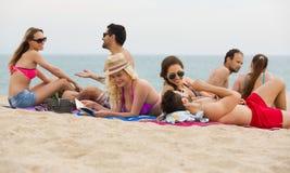 Folk som lägger på sand på stranden arkivbilder
