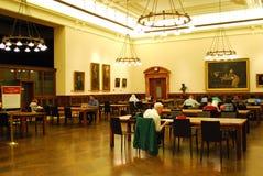 Folk som läser i offentligt biblioteknycen royaltyfri bild